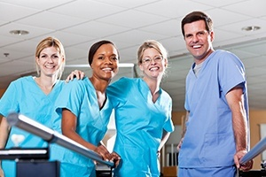 Four smiling dentists wearing blue scrubs