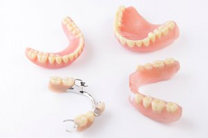 Full and partial dentures resting against neutral background