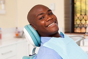 Man smiling in dentla chair after dental checkup and teeth cleaning