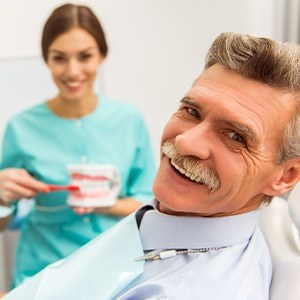 Older man in dental chair during restorative dentistry visit smiling