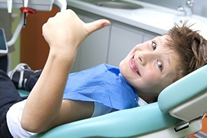 Child giving thumbs up during sedation dentistry visit
