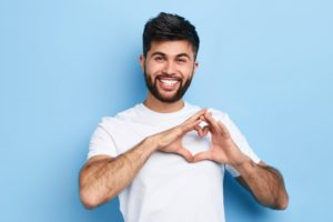 Man without gum disease making heart shape with hands